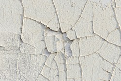 Close-up. Badly fixed white building facade wall covered with cracks in stucco. A big patch of paint missing on the middle.