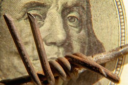 Close up barbed wire against blurred one hundred US Dollar bill as symbol of economic warfare, sanctions and embargo busting. Selective focus.