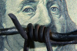 Close up barbed wire against US Dollar bill as symbol of economic warfare and sanctions. Horizontal image.