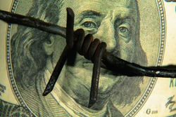 Close up barbed wire against US Dollar bill as symbol of economic warfare and sanctions. Selective focus. Horizontal image.