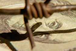 Close up barbed wire and US Dollar bill as symbol of economic warfare, sanctions and embargo busting. Selective focus on money. Horizontal image.