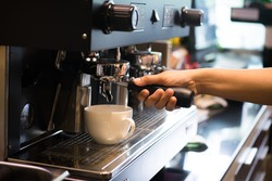 Close up barista hands making coffee by machine in coffee cafe. It's coffeemakers are cooking appliances used to coffee. Making Coffee Preparation Service Concept