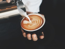 Close up barista hands pouring warm milk in coffee cup for making latte art.