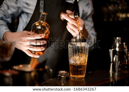 Close up. Barman in black apron carefully pours brown alcoholic drink to glassy shaker using beaker.