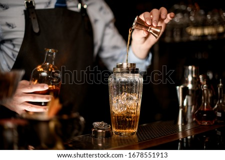 Close-up bartender using beaker pours brown alcoholic drink into glass shaker with one hand and holds bottle in other.