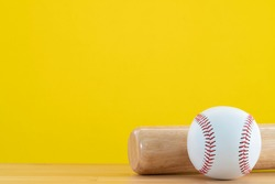Close up baseball and baseball bat on wooden table with yellow copy space background, sport concept