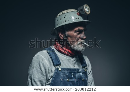 Close up Bearded Elderly Male Gold Miner Smoking a Cigarette While Facing to the Right of the Frame Against Black Gradient Background