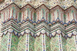 Close up beauitful mosaic tiles or colorful floral pattern decor on stupas in Wat Pho, temple in Bangkok, Thailand. Handmade or craft vintage styles.