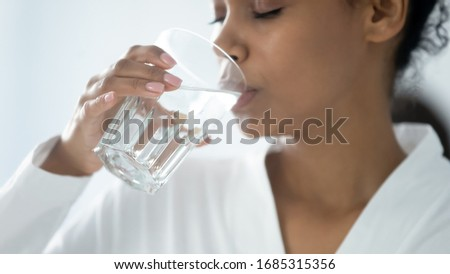 Close up beautiful african woman holding glass drinking a pill with still water. Minerals and vitamins for female, dietary supplement, reducing of thirst, body water balance healthy lifestyle concept
