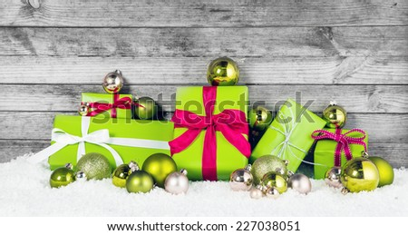 Close up Beautiful Apple Green Christmas Decorations with Assorted Size Presents and Balls on Snow. Display with Wooden Background.