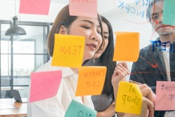 Close up Beautiful  Asian woman a writing glass wall with sticky notes in modern office,Asian business lifestyle concept