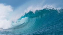 CLOSE UP: Beautiful deep blue tube wave in the wild Pacific Ocean curls towards a remote tropical island on a sunny day in summer. Spectacular shot of wild barrel wave coming from the exotic sea.