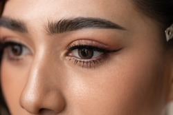 Close Up Beautiful eyes asian woman with contact lens. Charming beautiful young lady get brown contact lens. Attractive asian girl has nice makeup for party tonight. She use makeup artist service