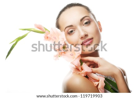 Close-up beautiful fresh face with pink gladiolus flowers in her hands