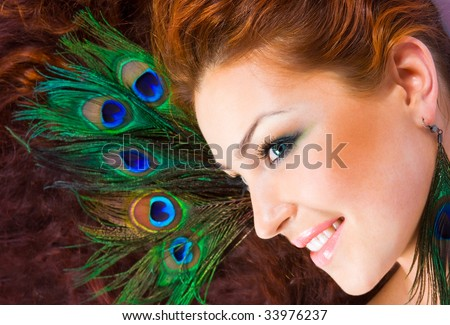 Close-up beautiful luxury red-hared model with perfect make-up with peacock feather in her hair and peacock earrings