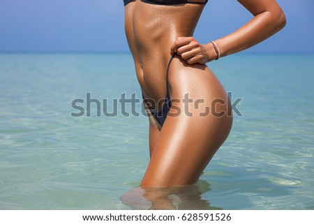 Close-up beautiful luxury slim girl in a bikini on the beach the ocean. Sexy tanned body, flat stomach, perfect figure.  #628591526