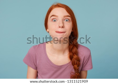 Photo of  Close up beautiful red-haired girl with her hair braided has fun stares at the camera dressed in an casual T-shirt ate something tasty delicious licked with pleasure isolated on a blue background.