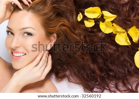 Close-up beautiful red-haired lady with yellow rose petals in her hair