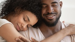 Close up beautiful serene african couple embracing closed eyes enjoy tender moment of unity and tenderness, enamored woman and man sharing lives and days, endearment and fidelity, forever love concept