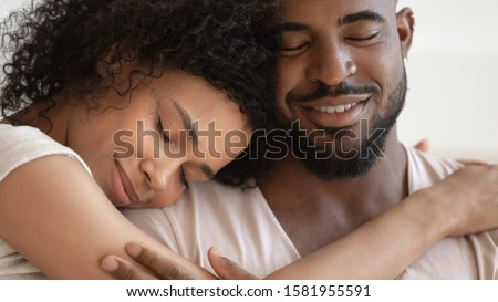 Photo of  Close up beautiful serene african couple embracing closed eyes enjoy tender moment of unity and tenderness, enamored woman and man sharing lives and days, endearment and fidelity, forever love concept