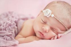 Close-up beautiful sleeping baby girl. Newborn baby girl, asleep on a blanket. A portrait of a beautiful, seven day old, newborn baby girl wearing a large, fabric rose headband. Closeup photo
