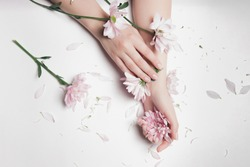 Close-up beautiful sophisticated female hands with pink flowers on white background. Concept hand care, anti-wrinkles, anti-aging cream, spa.