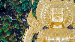 Close up beautiful Thai traditional golden Buddha statue with blurred mural painting on temple wall background