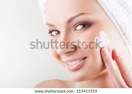 Close-up beautiful woman applying moisturizer cosmetic cream on face on light background - stock photo