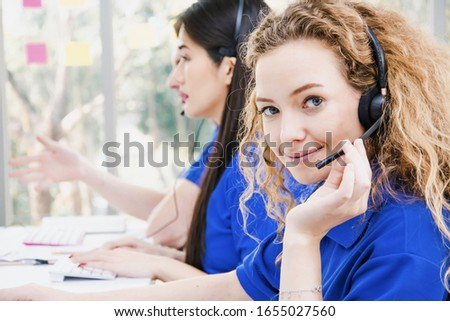 Close up beautiful woman customer service center staff happily smile with office headset,call center and provide after sales information,with team of staff,helping answer call and telephone marketing