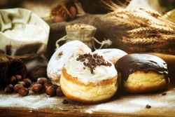 Close up. Beautifully arranged delicious donuts with icing, sugar, melted and sprinkled chocolate. Natural wooden background. Ideal for bakers, pastry shops or junk food, cheating on diet texts.
