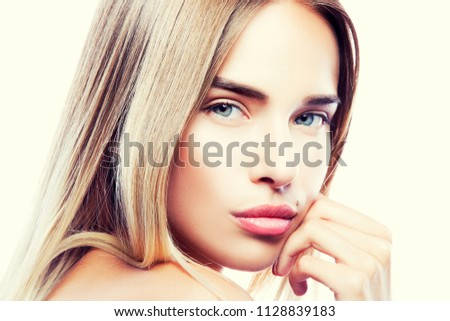 Stock Photo Close-up beauty girl face with perfect skin. Young fashion model woman. Blonde hair, blue eyes. natural nude make-up, beauty spot near mouth, hand near lips. Skincare facial treatment concept