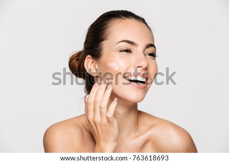 Close up beauty portrait of a laughing beautiful half naked woman applying face cream and looking away isolated over white background