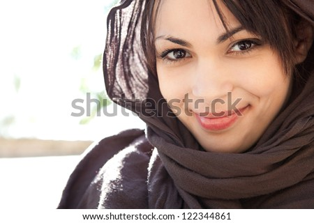Close up beauty portrait of a muslim young woman wearing a head scarf and smiling at the camera, outdoors.