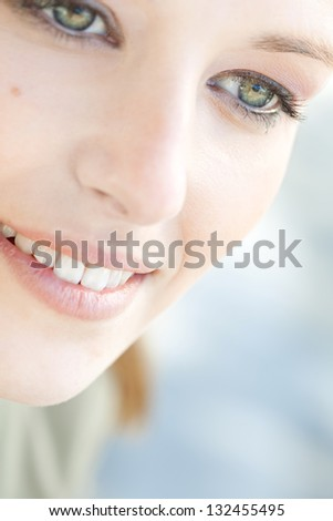 Close up beauty portrait of a young caucasian healthy woman face and eye looking down with long eyelashes.