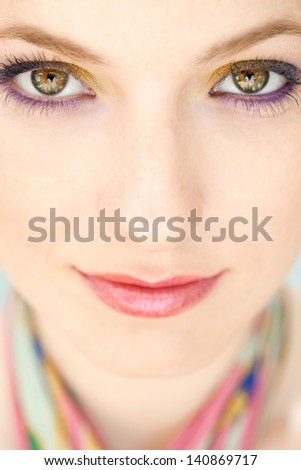 Close up beauty portrait of a young woman face wearing blue and yellow make up eyeshadow cosmetics looking at camera and softly smiling.