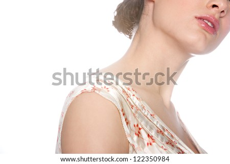 Close up beauty portrait of a young woman's neck, shoulders and lips glowing against a white background.
