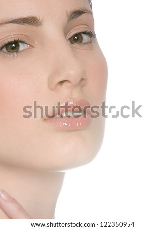 Close up beauty portrait of a young woman wearing glossy lipstick against a shining white background.