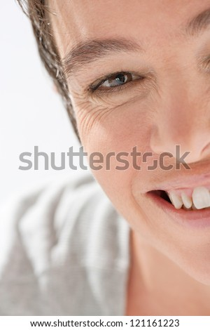 Close up beauty portrait of an attractive mature woman half face wearing a grey cotton robe and smiling at the camera.