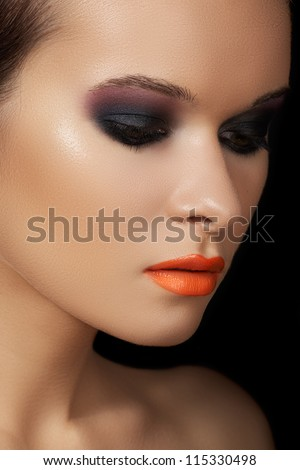 Close-up beauty portrait of attractive model face with bright make-up. Dark smoky eyes makeup, black ad purple eyeshadows, orange lips. Fashion witch style visage for Halloween