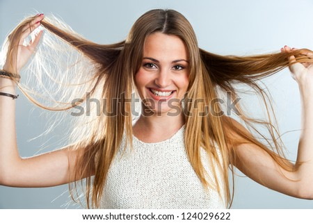 Close up beauty portrait of girl playing with long hair.
