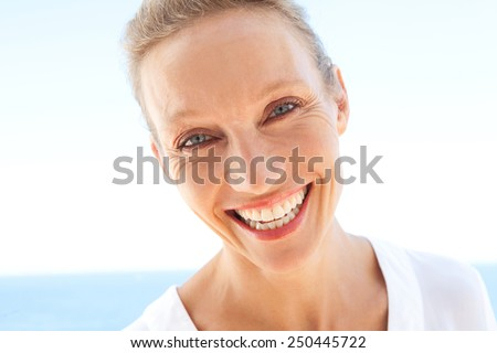 Close up beauty portrait of happy and joyful woman showing a fun and carefree expression of joy against a blue sky and sea background. Feelings and emotions in lifestyle. Gestures and expressions.
