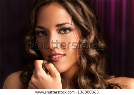 Close up beauty portrait of sensual brunette with curly hair.