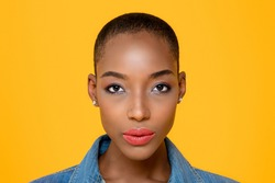 Close up beauty portrait of young African American woman looking at camera in isolated studio yellow background