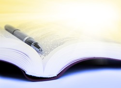 Close-up Bible with pen with yellow rays