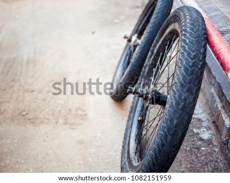close up bicycle parts outdoors on the ground tires wheels and rudder #1082151959