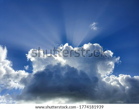 CLOSE UP Big white and grey cumulus cloud completely covers the summer sun shining down on earth. Few bright rays of sun shine past a massive cloud drifting over the clear blue sky. Idyllic cloudscape Photo stock ©