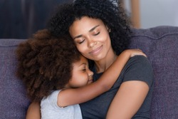 Close up biracial family portrait loving mother and little daughter sitting on couch at home hugging with closed eyes. Love, new mom for adopted child, warm relationships, caring elder sister concept