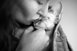 Close up, black and white photo of a woman kissing cute Devon Rex cat, love and tender mood image