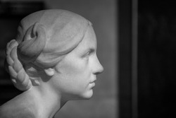 Close up, black and white picture of the white marble young woman isolated on dark background with long hair. Antique Roman statue. Milan, Lombardy, Italy.