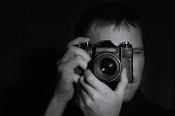 Close-up black and white portrait of a photographer with an old SLR camera in his hands on a dark background. Makes a horizontal frame in the studio